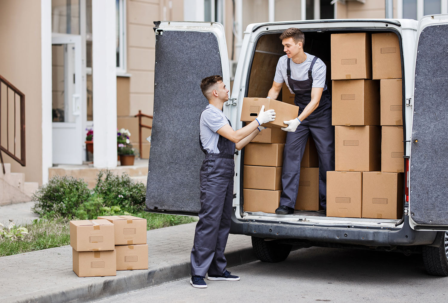 [:pl]Two young handsome movers wearing uniforms are unloading the van[:]