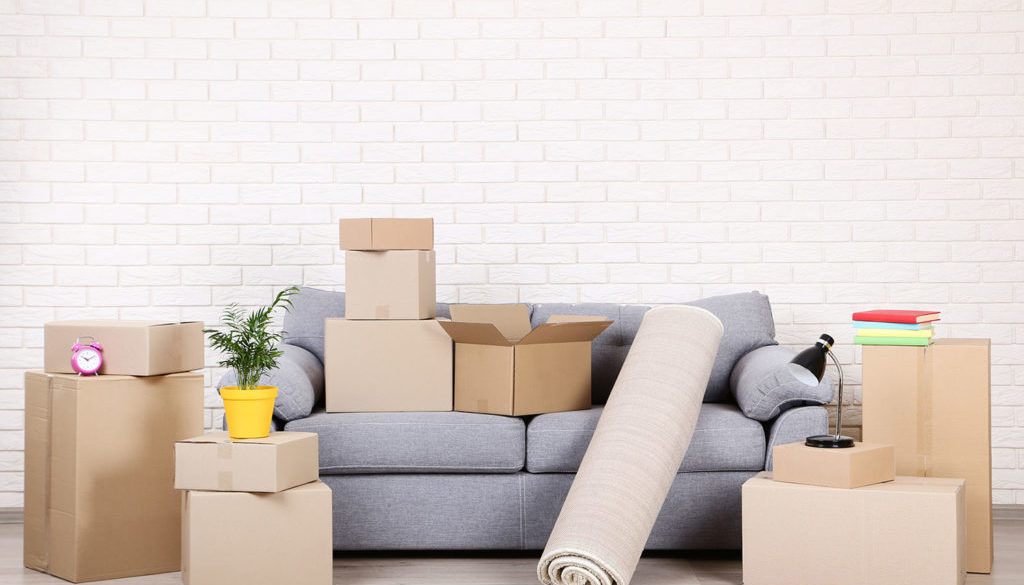 [:pl]Cardboard boxes with household stuff and grey sofa on brick wall background[:]