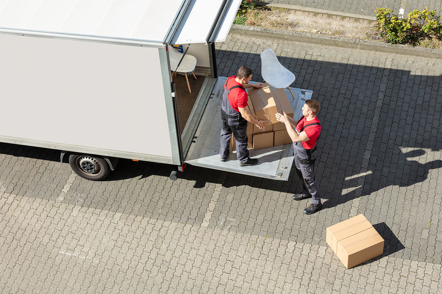[:pl]Male Movers Unloading The Cardboard Boxes Form Truck[:]